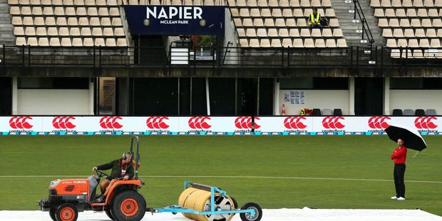 Ground staff tend to the covers in the washed out game at McLean Park. Photo / Getty