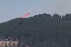 A helicopter pilot is dead as fire crews still battle a massive scrub fire on the Port Hills today