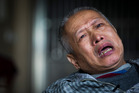 Bo Tu cries over the death of his daughter in his Wuhan home.