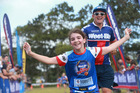 A competitor celebrates coming through the finish line at this year's Weet-Bix Kids TRYathalon today in Point England Auckland. Photo / Doug Sherring