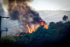 Firefighters and helicopters fight the blaze on the Port Hills Christchurch. Photo / Martin Hunter