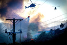 Fire fighters and helicopters fight the blaze on the Port Hills Christchurch around Osterholts Road, Tai Tapu. Photo / Christchurch Star, Martin Hunter