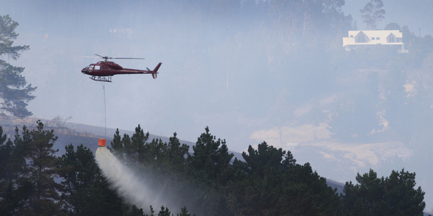 Helicopters are hard at work bushfires in the Port Hills above Christchurch. Photo / Alan Gibson.