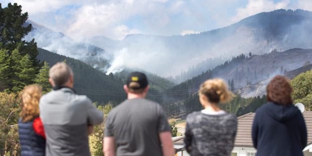Loading People watch as helicopters fight the bushfires raging in the Port Hills above Christchurch. Photo / Alan Gibson