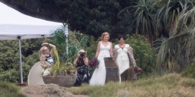 Anika Moa and Natasha Utting pose for photos before their wedding at Bethells Beach on Saturday with close friends. Photo / Greg Bowker