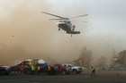 A helicopter kicks up dust as it lands at a staging area near the Oroville Dam. Photo / AP