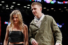 Genie Bouchard, walks the court with her blind date, John Goehrke, right, during the first half of an NBA basketball game between the Brooklyn Nets and the Milwaukee Bucks. Photo / AP.