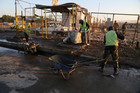 Municipality workers clean up the aftermath of a suicide car bomb attack at a used cars dealers parking lot in the eastern Habibiya neighborhood of Baghdad, Iraq. Photo / AP