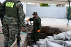 Greek Army officers conduct preparation work before they excavate an unexploded World War II bomb. Photo / AP