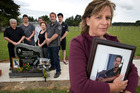 Judy Richards (foreground) pictured holding a photograph of her son Rhys Middleton while other family members gather around the headstone at his graveside in Tauranga. Photo/file