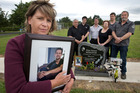 Judy Richards holding a photograph of her son Rhys Middleton while other family members gather around the headstone at his graveside in Tauranga. Photo/File