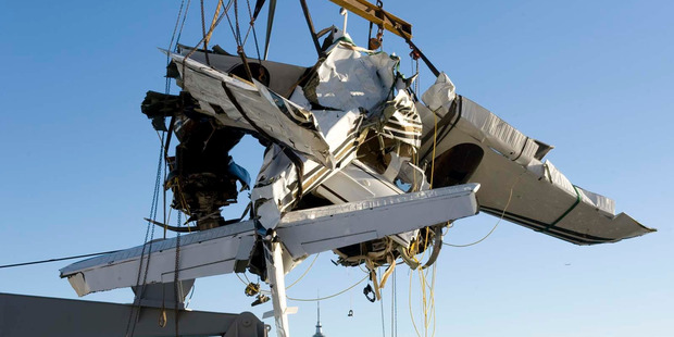 The wreckage of the Beechcraft Baron that crashed with 2degrees boss Eric Hertz and his wife Kathy Hertz on board being lifted from HMNZS Manawanu at the naval base in Devonport in April 2013.  Photo / NZ Navy