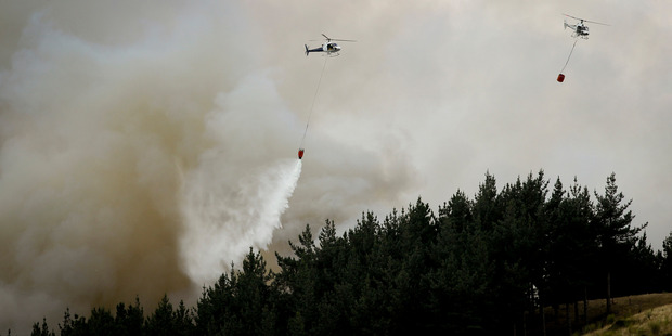 Helicopters with monsoon buckets drops water over burning pine trees near Waimarama Rd, south of Hastings, this week. Photo / File