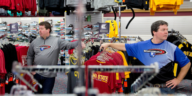 Brothers Todd, right, and Scott Yeomans, owners of a custom sportswear company, stand in their store in Prairie du Chien, Wis. Photo / AP