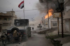 A car bomb explodes next to Iraqi special forces armored vehicles as they advance towards Islamic State militant. Photo / AP