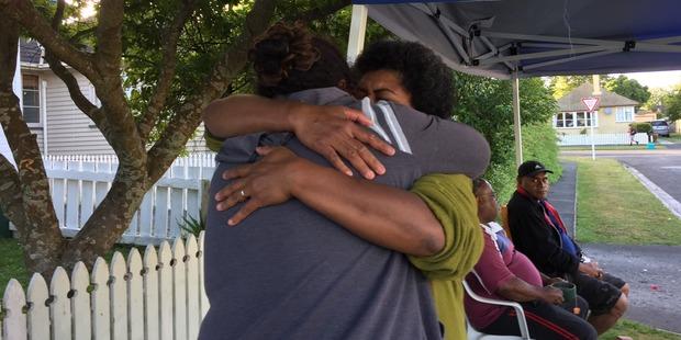 Adi Inoke is hugged by a friend when she learns her daughter is safe. Photo / Belinda Feek