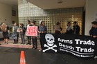 Protesters sporting signs have this morning gathered outside the Wellington District Court where 16 peace protesters are to go on trial. Picture / Melissa Nightingale