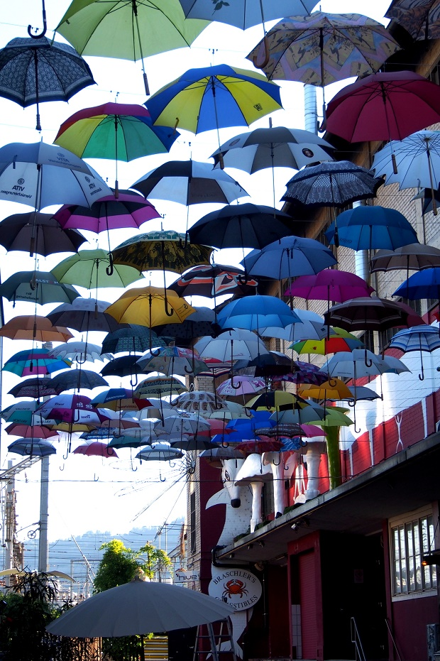 Gerold Chuchi bar in Zurich, with an installation brightly coloured umbrellas hung overhead in the alley outside.