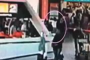 A woman white top creeps up behind Kim Jong-nam and appears to spray something in his face. Photo / CCTV