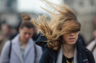 A commuter's hair blows in the wind as they cross London Bridge. Photo / Getty Images