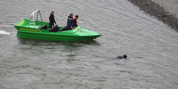 The Police Dive Squad search the river under Ballance Bridge in the Manawatu Gorge.