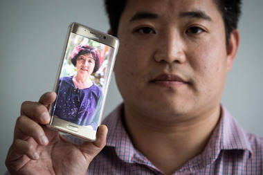 Chen Wang says his mother (pictured on his phone) cannot visit him in New Zealand because she suffers from hepatitis B and C. Photo / Jason Oxenham