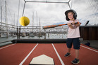 Ryder Beard, 4, takes a swing in the baseball batting cage set up in Wynyard Quarter. Photo / Nick Reed