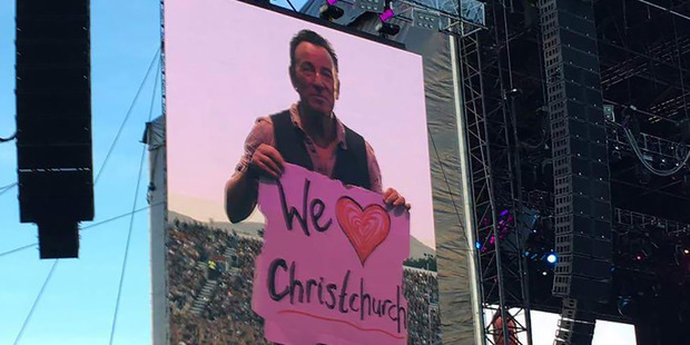 Bruce Springsteen held up a We love Christchurch sign, to applause from the crowd. Photo / Tania Gibson