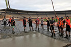 TEAM EFFORT: Volunteers helped contractors drain the track and lay concrete for the D1NZ National Drifting Championship to be held at Baypark on Friday and Saturday. PHOTO: SUPPLIED