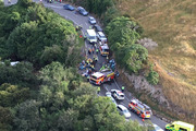 Emergency services freed several people trapped in the wreckage after a car and a bus carrying 33 tourists collided. Photo / Broadcast Media - Matthew Simons