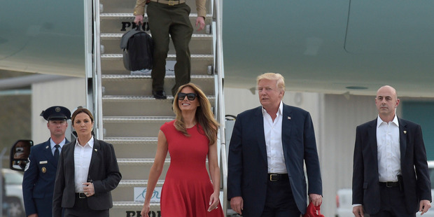 President Donald Trump and first lady Melania Trump walk off of Air Force One to speak at the 'Make America Great Again Rally'. Photo / AP
