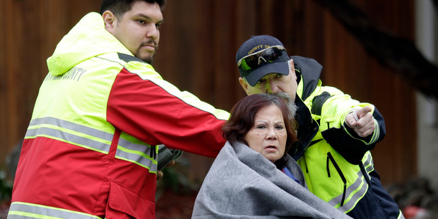 A woman is directed to a safe zone by rescue crews after being rescued by boat from a flooded neighbourhood in San Jose. Photo / AP