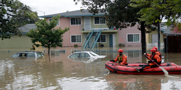 Rescuers travel by boat through a flooded neighbourhood looking for stranded residents in San Jose, California. Photo / AP