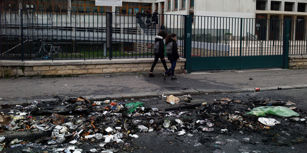 Students walk past debris in front of the Henri Bergson college after a protest against alleged police abuses. Photo / AP