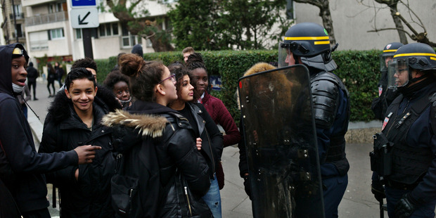 Students talk with a riot police officer as they protest against alleged police abuses in front of the Henri Bergson college, in Paris. Photo / AP