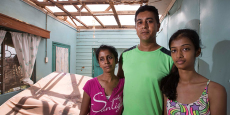 In the room of their Rakiraki home where they tried to shelter from the cyclone are Salesh Kumar, his wife Premila and daughter Priyashna. Photo / Brett Phibbs