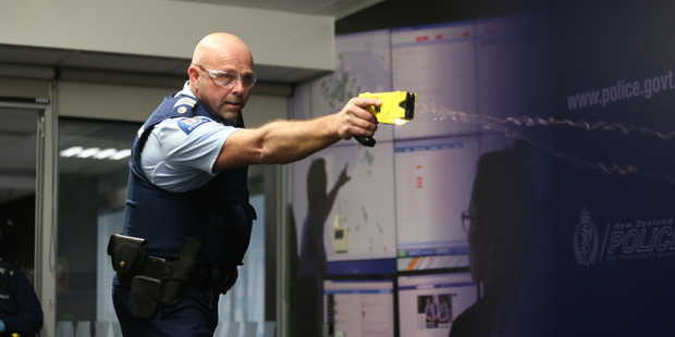 A police officer demonstrates the use of a taser at Police National Headquarters in Wellington. New Zealand Herald Photograph by Mark Mitchell.