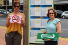 Rotorua Lakes Council staff Rachel Doelman (left) and Rosemary Viskovic with smokefree signage at Arawa Street bus stop. PHOTO/SUPPLIED