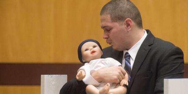 Tony Moreno demonstrates to the jury how he held his son Aaden on the railing of the Arrigoni Bridge. Photo / AP