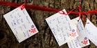 Notes to lost loved ones were attached to a tree opposite the Christchurch earthquake memorial wall. Photo / Christchurch Star