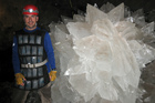Researcher Mario Corsalini stands by giant gypsum rosette crystals in the Naica mine in Chihuahua, Mexico. Photo / AP