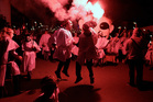 Two men sing and dance during the Torch Parade on the Greek island of Naxos. Photo / AP