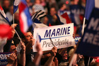Supporters of far-right French leader presidential candidate Marine Le Pen wave banners as she speaks in Nantes, western France. Photo / AP