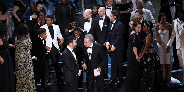 Host Jimmy Kimmel and presenter Warren Beatty discuss the results of best picture as the casts of La La Land and Moonlight mingle on stage. Photo/AP