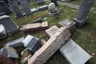 Damaged headstones rest on the ground at Mount Carmel Cemetery in Philadelphia. Photo / AP