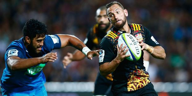 Aaron Cruden of the Chiefs beats the tackle of Akira Ioane of the Blues. Photo / Getty