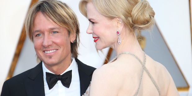 Singer Keith Urban (L) and actress Nicole Kidman arrive at the Oscars with a criss-cross styled dress. Photo /Getty