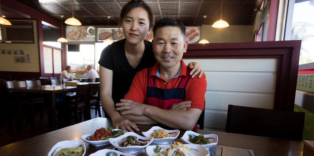 Stella Lee and her dad, Sang Jo Lee, with a selection of side dishes from Kumkang Mountain Korean Restaurant in Albany. Their restaurant has a policy that each customer must order at lest one main meal.