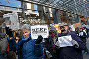 People with taped mouths hold signs and a copy of the New York Times as they show solidarity with the press during a rally in front of The New York Times building. Photo / AP