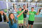 Trojan swimmers Bianca Van Zyl, 11, Michael Landsdown 12, coach Daniel Bell, and Tobias Leiser, 11, who won won 17 medals at the NZ Junior Festival in Wellington. PHOTO/Warren Buckland
